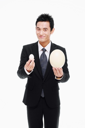 Businessman holding a big and a small egg photo