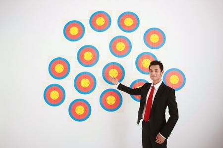 Businessman showing a wall of targets photo