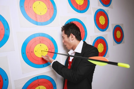 Businessman looking at arrow on bulls-eye of target photo