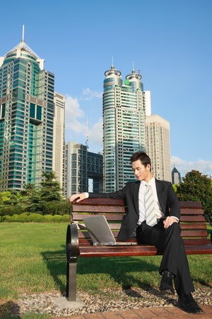 banc de parc: Homme d'affaires utilisant un ordinateur portable dans le parc
