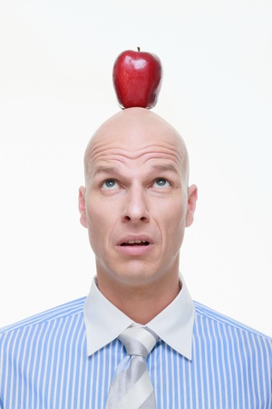 Man looking up at apple on the top of his head photo