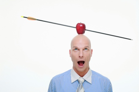 Man with apple pierced by arrow balanced on his head photo