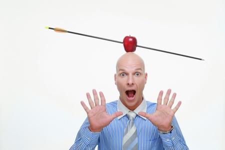 Man with apple pierced by arrow balanced on his head photo