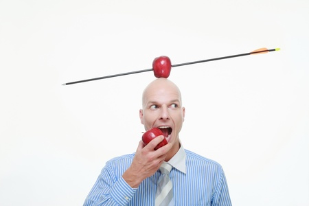 Man eating apple with apple pierced by arrow balanced on his head photo