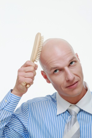 Bald man combing his head