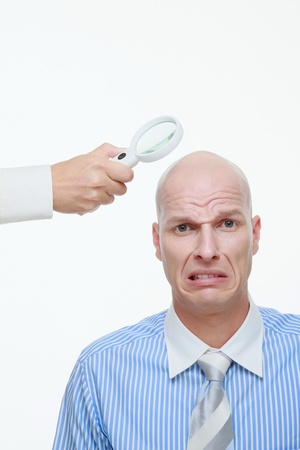 Hand holding a magnifying glass near a bald mans head photo