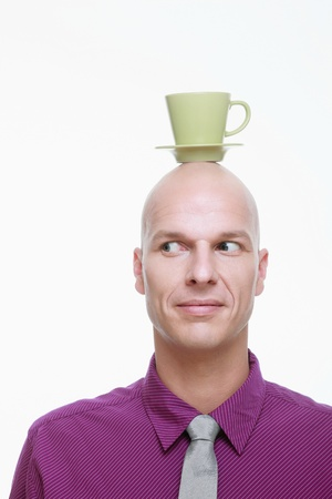 Man with cup and saucer balanced on his head photo