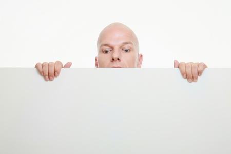 Businessman peeking from behind white placard photo