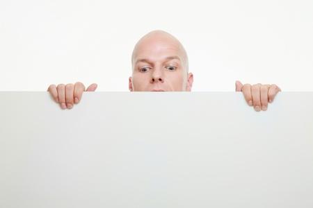 Businessman peeking from behind white placard photo