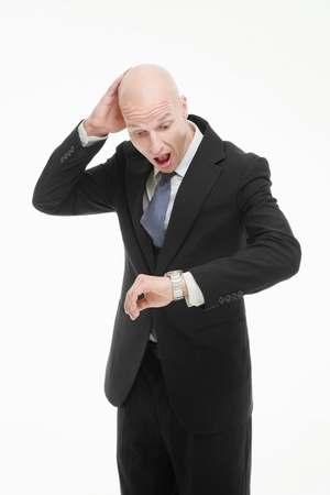 Businessman scratching head while checking the time on his watch photo