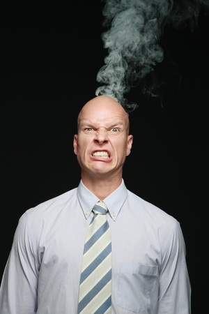 clenching teeth: Smoke coming out of businessmans head Stock Photo