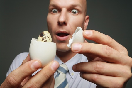 discovering: Businessman discovering a quail egg inside a chicken egg Stock Photo