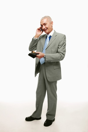 Businessman talking on the phone while holding wallet containing credit card photo