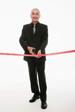 Businessman cutting red ribbon Stock Photo - 9525400