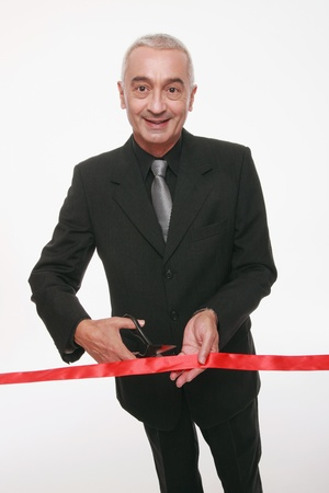 Businessman cutting red ribbon photo