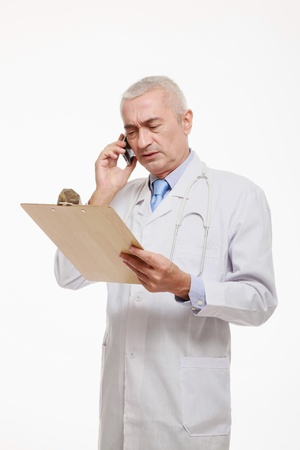 Doctor talking on the mobile phone while looking at clipboard photo