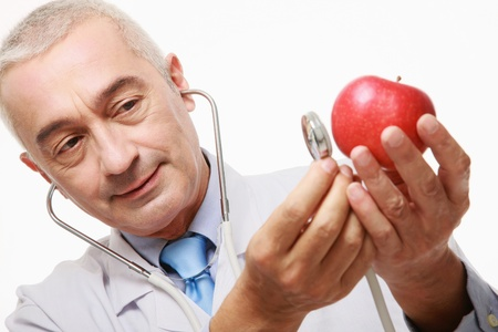 Doctor listening to an apple with stethoscope  photo