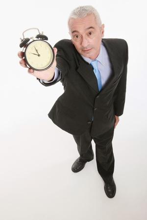 Businessman holding up an alarm clock photo