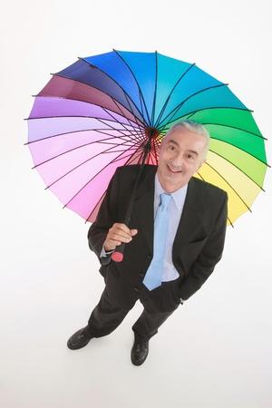 Businessman holding a colourful umbrella photo