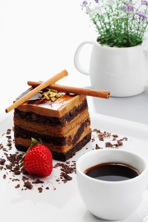Chocolate coffee layered cake with a cup of coffee photo