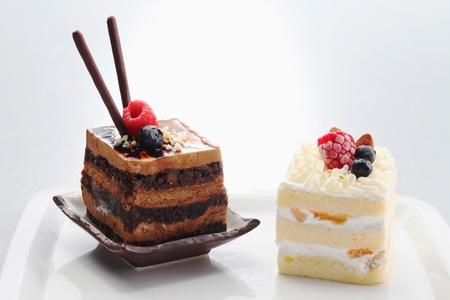 pretzel stick: Chocolate coffee layered cake and white chocolate apricot cake Stock Photo