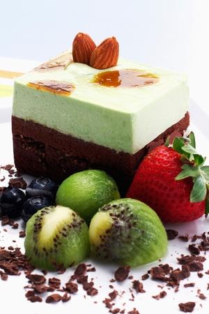 Pistachio chocolate cake with fruit garnishing and chocolate flakes