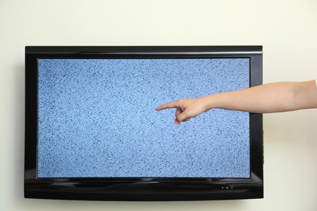 Mans hand pointing at ruined television photo