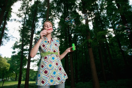Woman blowing soap bubbles photo