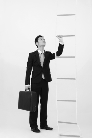 rope ladder: Businessman with briefcase looking at rope ladder Stock Photo