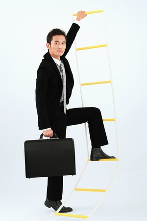 Businessman climbing up rope ladder photo