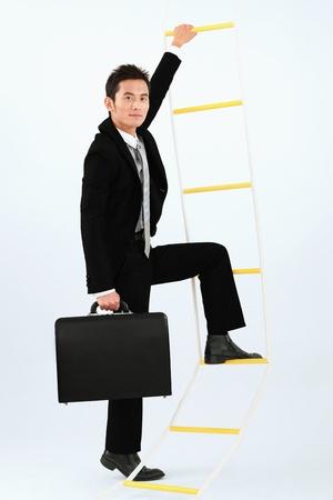 Businessman climbing up rope ladder photo