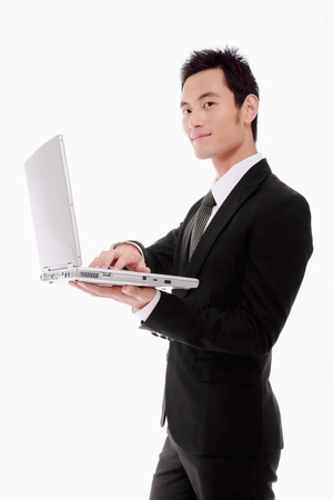 Businessman standing and using laptop photo