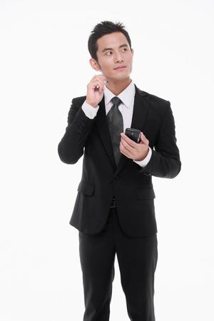 Businessman thinking while using electronic organizer photo