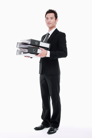 Businessman holding stack of files photo