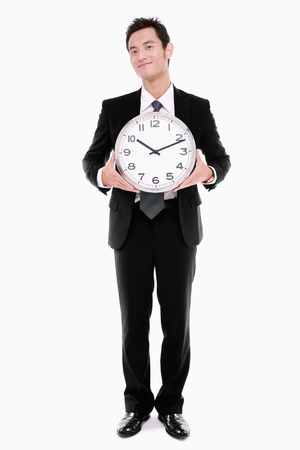 Businessman holding clock photo