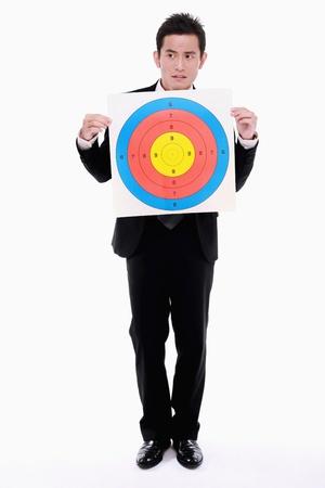 Businessman holding target photo