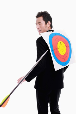 Arrow flying toward target on the back of businessman photo