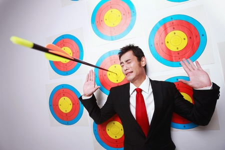 office politics: Businessman on target with arrow next to him Stock Photo