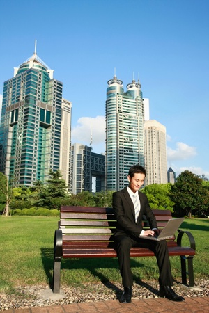 Businessman using laptop in the park Stock Photo - 9604593