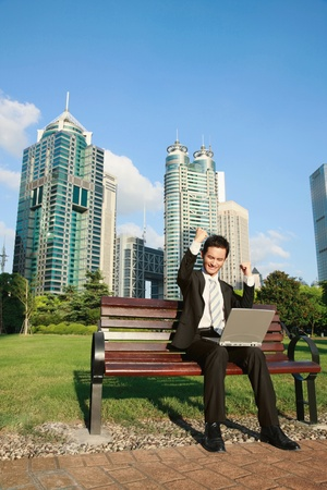 Businessman punching the air while using laptop photo