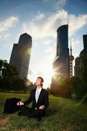 Businessman meditating in the park photo