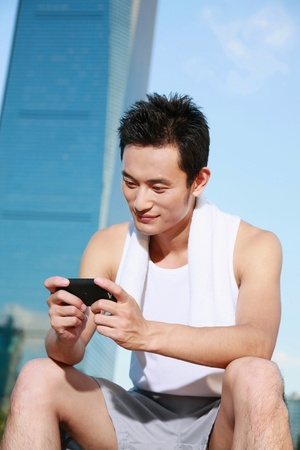 Man in sports clothing text messaging on the phone photo