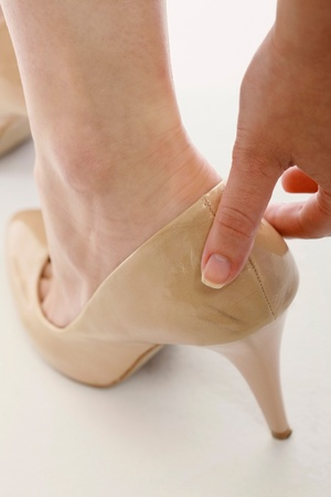 Woman wearing stilletoe shoes with sore heel