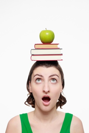 Woman balancing a stack of books and green apple on her head photo