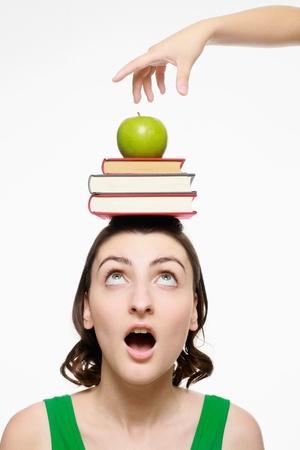 femme regarde en haut: Main sur le point de prendre apple du dessus de la t�te de femme, femme � la recherche en �tat de choc