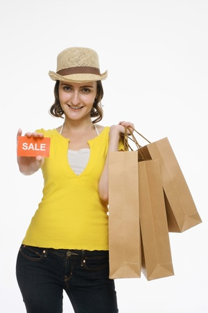 Woman holding sale sign while carrying shopping bags photo