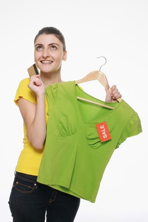 Woman holding blouse on sale and credit card while thinking photo