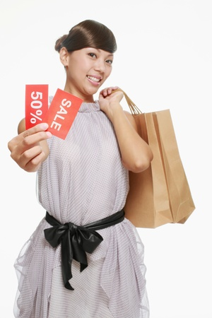 Woman holding sale sign while carrying shopping bags. photo
