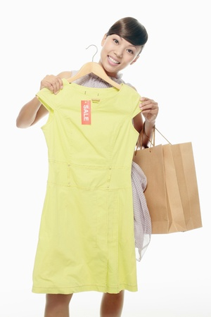 Woman holding dress on sale in front of her photo