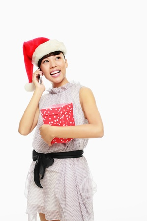 Woman with santa hat talking on the phone and holding present photo